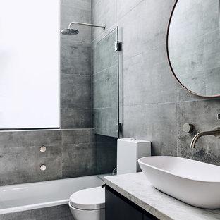 Foto de cuarto de baño actual con armarios con paneles lisos, puertas de armario negras, bañera encastrada, combinación de ducha y bañera, baldosas y/o azulejos grises, paredes grises, suelo de cemento, lavabo sobreencimera, suelo gris y encimeras blancas