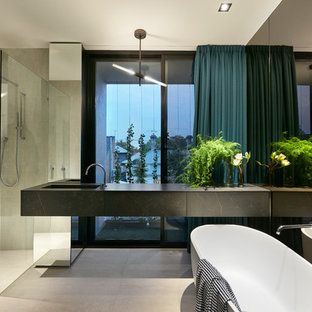 Design ideas for a large contemporary master bathroom in Melbourne with furniture-like cabinets, black cabinets, a freestanding tub, an open shower, a wall-mount toilet, gray tile, porcelain tile, grey walls, porcelain floors, an integrated sink, engineered quartz benchtops, grey floor, an open shower and black benchtops.