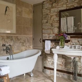 Kleines Duschbad mit Löwenfuß-Badewanne, Steinplatten, beiger Wandfarbe, beigefarbenen Fliesen, Waschtischkonsole und beigem Boden in Sonstige