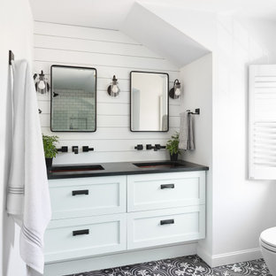 Bathroom - coastal black floor, double-sink and shiplap wall bathroom idea in Boston with shaker cabinets, white cabinets, white walls, an undermount sink, black countertops and a floating vanity