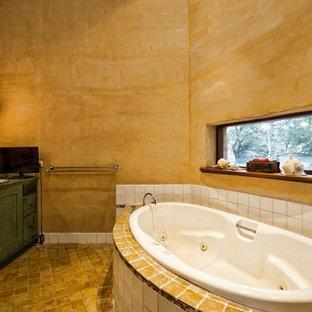 Diseño de cuarto de baño principal, rural, grande, con armarios tipo mueble, puertas de armario con efecto envejecido, bañera encastrada, baldosas y/o azulejos blancos, baldosas y/o azulejos de porcelana, paredes beige, lavabo encastrado, suelo amarillo y encimeras turquesas
