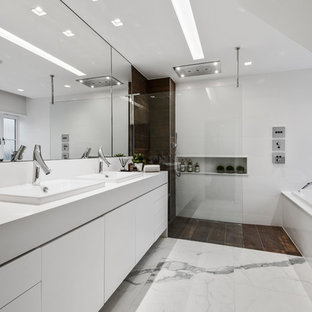 This is an example of a large contemporary ensuite bathroom in West Midlands with white cabinets, a wall mounted toilet, white tiles, white walls, an open shower, white worktops, flat-panel cabinets, a built-in bath, a walk-in shower, a built-in sink and white floors.