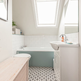 This is an example of a contemporary bathroom in London with white tiles, ceramic tiles, porcelain flooring, flat-panel cabinets, white cabinets, a built-in bath, white walls, a console sink and grey floors.