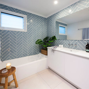 Design ideas for a mid-sized beach style 3/4 bathroom in Sunshine Coast with white cabinets, blue tile, ceramic tile, ceramic floors, an undermount sink, engineered quartz benchtops, beige floor, white benchtops, flat-panel cabinets, an alcove tub and blue walls.