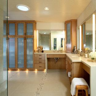 Diseño de cuarto de baño principal, actual, grande, con lavabo bajoencimera, armarios con paneles lisos, puertas de armario de madera oscura, baldosas y/o azulejos beige, suelo de baldosas tipo guijarro, ducha esquinera, baldosas y/o azulejos de piedra y paredes beige