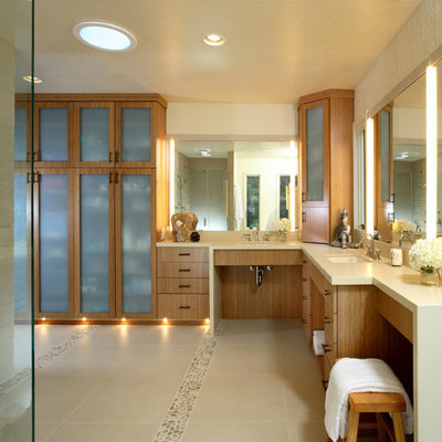Example of a large trendy master beige tile and stone tile pebble tile floor corner shower design in San Francisco with an undermount sink, flat-panel cabinets, medium tone wood cabinets and beige walls