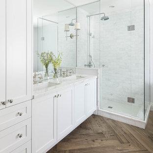 Ejemplo de cuarto de baño tradicional con lavabo bajoencimera, armarios estilo shaker, puertas de armario blancas, ducha esquinera, baldosas y/o azulejos blancos y suelo de madera oscura