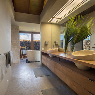 Island style master limestone floor and gray floor freestanding bathtub photo in Hawaii with medium tone wood cabinets, a vessel sink, wood countertops, flat-panel cabinets and beige walls