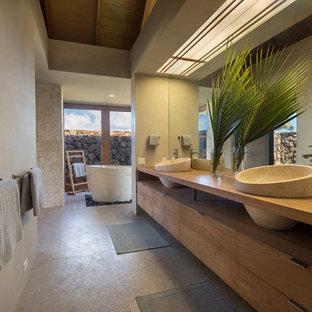 Foto på ett tropiskt en-suite badrum, med skåp i mellenmörkt trä, ett fristående badkar, kalkstensgolv, ett fristående handfat, träbänkskiva, grått golv, släta luckor och beige väggar