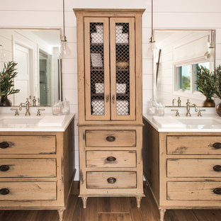 Photo of a coastal ensuite bathroom in Philadelphia with freestanding cabinets, distressed cabinets, white tiles, a submerged sink, brown floors, white walls and white worktops.
