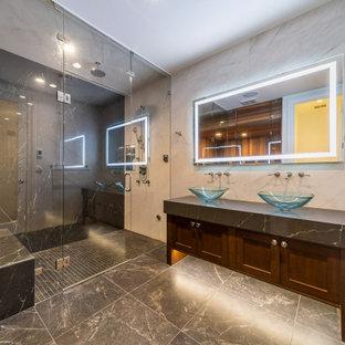 バンクーバーの中サイズのトランジショナルスタイルのおしゃれなサウナ (茶色いキャビネット、置き型浴槽、コーナー設置型シャワー、マルチカラーのタイル、磁器タイル、マルチカラーの壁、磁器タイルの床、クオーツストーンの洗面台、グレーの床、開き戸のシャワー、グレーの洗面カウンター) の写真