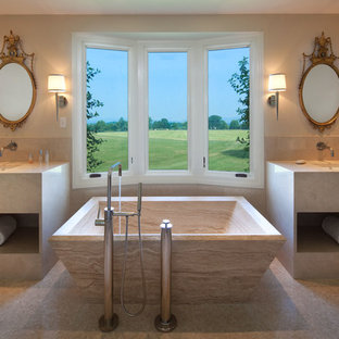 Inspiration for a large traditional ensuite bathroom in Richmond with a freestanding bath, flat-panel cabinets, beige cabinets, beige tiles, ceramic tiles, beige walls, a submerged sink and beige floors.