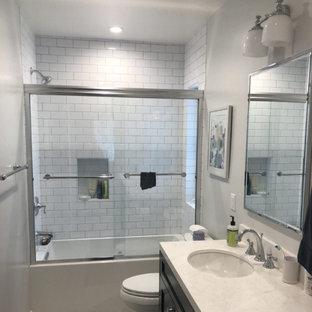Свежая идея для дизайна: ванная комната среднего размера в стиле модернизм с душем над ванной, белой плиткой, керамической плиткой, белыми стенами, белым полом, душем с раздвижными дверями, тумбой под одну раковину и кирпичными стенами - отличное фото интерьера
