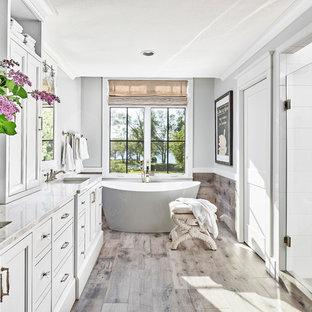 Immagine di una grande stanza da bagno padronale costiera con ante bianche, vasca freestanding, doccia alcova, piastrelle bianche, pareti grigie, pavimento in gres porcellanato, top in marmo, pavimento marrone, porta doccia a battente, top bianco e lavabo sottopiano