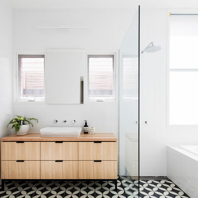 Example of a mid-sized trendy master white tile and porcelain tile mosaic tile floor and multicolored floor bathroom design in Melbourne with light wood cabinets, wood countertops, flat-panel cabinets, white walls and a vessel sink