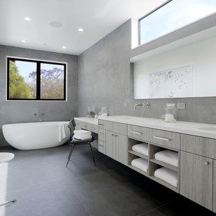 Idéer för funkis en-suite badrum, med släta luckor, grå skåp, grå väggar, skiffergolv, ett undermonterad handfat, grått golv, grå kakel och ett fristående badkar