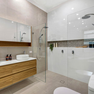 This is an example of a contemporary master bathroom in Adelaide with flat-panel cabinets, medium wood cabinets, a curbless shower, beige tile, multi-coloured tile, a vessel sink, engineered quartz benchtops, beige floor, an open shower, white benchtops, a double vanity and a floating vanity.