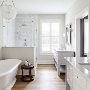 Inspiration for a large country master bathroom in Philadelphia with a freestanding tub, gray tile, marble, grey walls, light hardwood floors, an undermount sink, engineered quartz benchtops, a hinged shower door, furniture-like cabinets, grey cabinets, a corner shower, beige floor and grey benchtops.