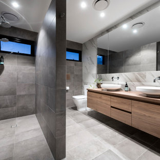 This is an example of a large contemporary master bathroom in Perth with flat-panel cabinets, medium wood cabinets, a corner shower, a one-piece toilet, gray tile, a vessel sink, wood benchtops, grey floor, an open shower, brown benchtops, a double vanity and a floating vanity.