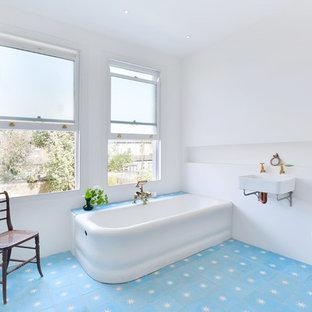 Mittelgroßes Modernes Duschbad mit Eckbadewanne, Wandtoilette, weißer Wandfarbe, Zementfliesen, Wandwaschbecken und blauem Boden in London