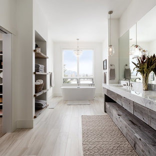 Traditional ensuite bathroom in Other with flat-panel cabinets, dark wood cabinets, a freestanding bath, white walls, a submerged sink, beige floors and white worktops.