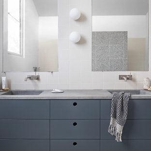 Modelo de cuarto de baño infantil, actual, grande, con bañera exenta, ducha abierta, suelo de terrazo, encimera de cemento, ducha abierta y encimeras grises