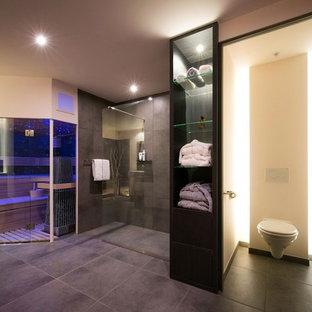 Immagine di un'ampia sauna minimalista con nessun'anta, ante in legno bruno, doccia a filo pavimento, WC sospeso, piastrelle grigie, piastrelle in ardesia, pareti beige, pavimento in ardesia, pavimento grigio e doccia aperta