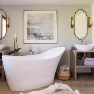 Cette photo montre une salle de bain principale chic de taille moyenne avec un placard en trompe-l'oeil, des portes de placard en bois clair, une baignoire indépendante, une douche ouverte, un WC suspendu, un carrelage bleu, un mur bleu, un sol en bois brun, une vasque, un plan de toilette en bois, un sol marron, aucune cabine et un plan de toilette marron.