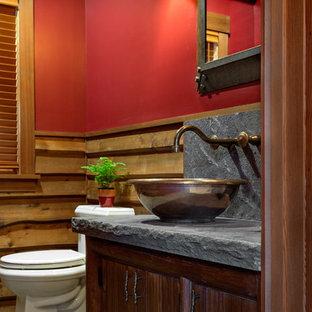 Modelo de cuarto de baño con ducha, rústico, de tamaño medio, con armarios con paneles empotrados, puertas de armario de madera en tonos medios, sanitario de una pieza, paredes rojas, suelo de baldosas de cerámica y encimera de granito