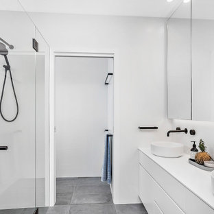 This is an example of a large contemporary 3/4 bathroom in Wollongong with flat-panel cabinets, white cabinets, a curbless shower, white walls, porcelain floors, a vessel sink, grey floor, a hinged shower door, white benchtops, a niche and a floating vanity.