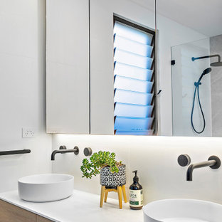 This is an example of a mid-sized contemporary master bathroom in Wollongong with flat-panel cabinets, white tile, porcelain tile, white walls, a vessel sink, white benchtops, a double vanity, a built-in vanity and medium wood cabinets.