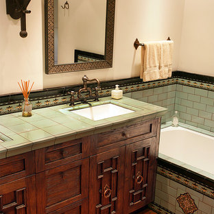 Mid-sized mediterranean master bathroom in Los Angeles with raised-panel cabinets, an undermount tub, multi-coloured tile, ceramic tile, beige walls, terra-cotta floors, an undermount sink, tile benchtops, brown floor and green benchtops.