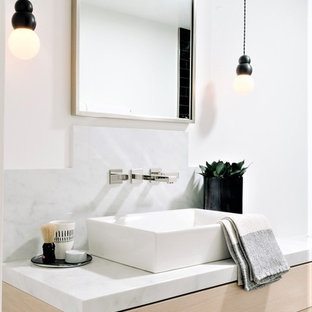 Bathroom - contemporary white tile bathroom idea in Orange County with light wood cabinets, white walls, a vessel sink and white countertops