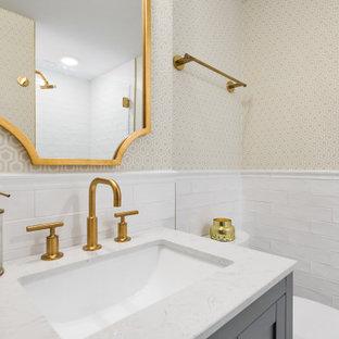 Idée de décoration pour une petit salle de bain tradition avec un placard à porte shaker, des portes de placard grises, un WC séparé, un carrelage blanc, un carrelage métro, un mur beige, un sol en marbre, un lavabo encastré, un plan de toilette en quartz modifié, un sol blanc, une cabine de douche à porte battante, un plan de toilette blanc, meuble simple vasque, meuble-lavabo sur pied et du papier peint.