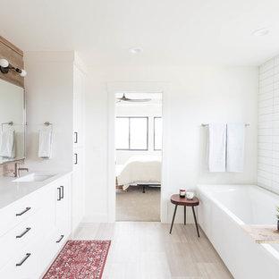 Idee per una stanza da bagno country con ante in stile shaker, ante bianche, vasca ad angolo, piastrelle bianche, pareti bianche, lavabo sottopiano, pavimento grigio e top bianco