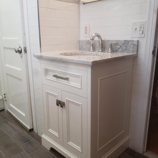 This is an example of a small traditional bathroom in New York with furniture-like cabinets, white cabinets, white tile, porcelain tile, laminate floors, an undermount sink, marble benchtops and white benchtops.