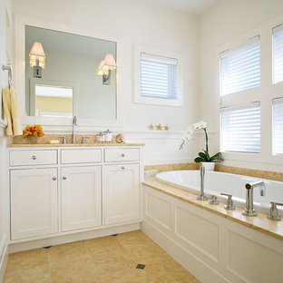 Coastal beige tile drop-in bathtub photo in New York with shaker cabinets and white cabinets