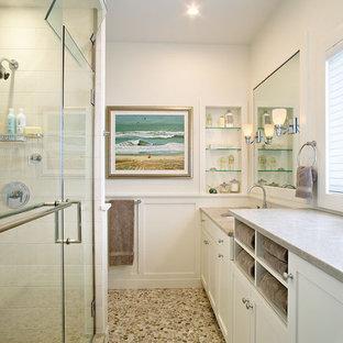 Immagine di una stanza da bagno costiera con lavabo sottopiano, ante in stile shaker, ante bianche, doccia alcova, piastrelle bianche e pavimento con piastrelle di ciottoli
