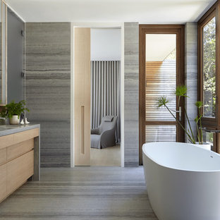 Example of a beach style master gray tile gray floor freestanding bathtub design in New York with gray countertops, flat-panel cabinets, light wood cabinets, gray walls and an undermount sink