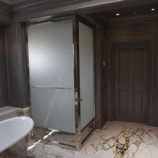 Diseño de cuarto de baño principal, tradicional, grande, con armarios con paneles empotrados, puertas de armario grises, bañera exenta, ducha esquinera, paredes grises, suelo de baldosas de porcelana y encimera de ónix