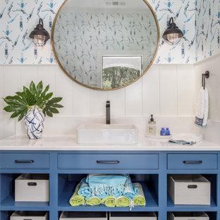 Foto de cuarto de baño costero con armarios con rebordes decorativos, puertas de armario azules, paredes blancas, lavabo sobreencimera, suelo negro y encimeras blancas