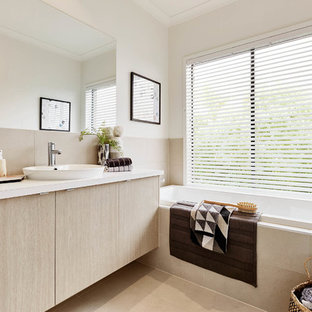 Photo of a contemporary bathroom in Melbourne with flat-panel cabinets, beige cabinets, a drop-in tub, white walls and a drop-in sink.