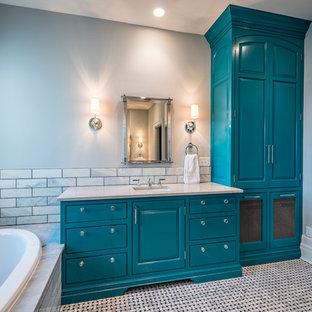 Diseño de cuarto de baño principal, tradicional, de tamaño medio, con armarios con paneles con relieve, puertas de armario azules, bañera encastrada, baldosas y/o azulejos grises, baldosas y/o azulejos de mármol, paredes grises, suelo de mármol, lavabo bajoencimera, encimera de mármol, suelo gris y encimeras grises