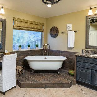 Foto på ett vintage en-suite badrum, med luckor med upphöjd panel, skåp i slitet trä, ett badkar med tassar, gula väggar, ett undermonterad handfat och granitbänkskiva