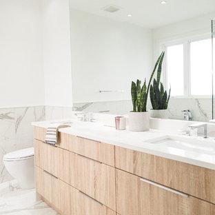 Foto på ett stort funkis vit en-suite badrum, med släta luckor, skåp i ljust trä, vita väggar, ett undermonterad handfat, vitt golv, ett fristående badkar, en öppen dusch, en toalettstol med hel cisternkåpa, grå kakel, vit kakel, stenkakel, marmorgolv, bänkskiva i kvarts och dusch med gångjärnsdörr