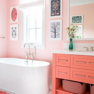 Modelo de cuarto de baño infantil, de estilo de casa de campo, de tamaño medio, con armarios estilo shaker, bañera exenta, paredes rosas y encimeras blancas