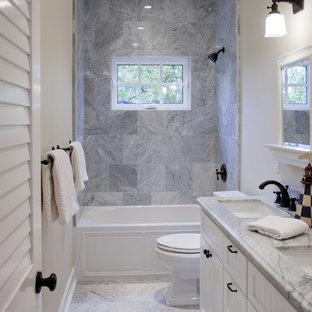 Modelo de cuarto de baño marinero con puertas de armario blancas, bañera empotrada, combinación de ducha y bañera, baldosas y/o azulejos grises y encimeras grises