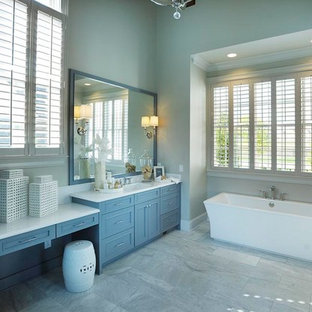 Inspiration for a mid-sized farmhouse master gray tile and stone tile ceramic floor freestanding bathtub remodel in Nashville with flat-panel cabinets, gray cabinets, quartzite countertops, gray walls and an undermount sink