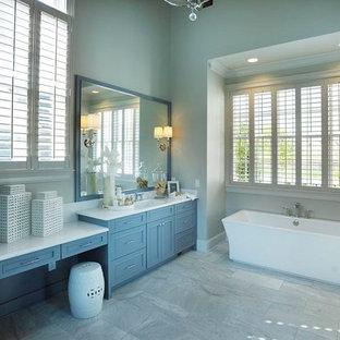 ナッシュビルの中サイズのカントリー風おしゃれなマスターバスルーム (フラットパネル扉のキャビネット、グレーのキャビネット、珪岩の洗面台、置き型浴槽、グレーのタイル、グレーの壁、セラミックタイルの床、石タイル、アンダーカウンター洗面器) の写真