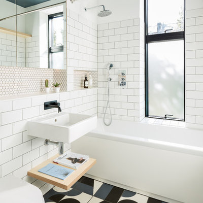 Example of a mid-sized danish white tile and subway tile ceramic tile and multicolored floor bathroom design in London with white walls, a wall-mount sink and a wall-mount toilet
